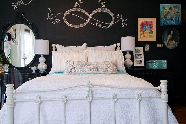 An-all-white-bed-sits-in-front-of-a-black-chalkboard-wall-in-the-small-bedroom.jpg